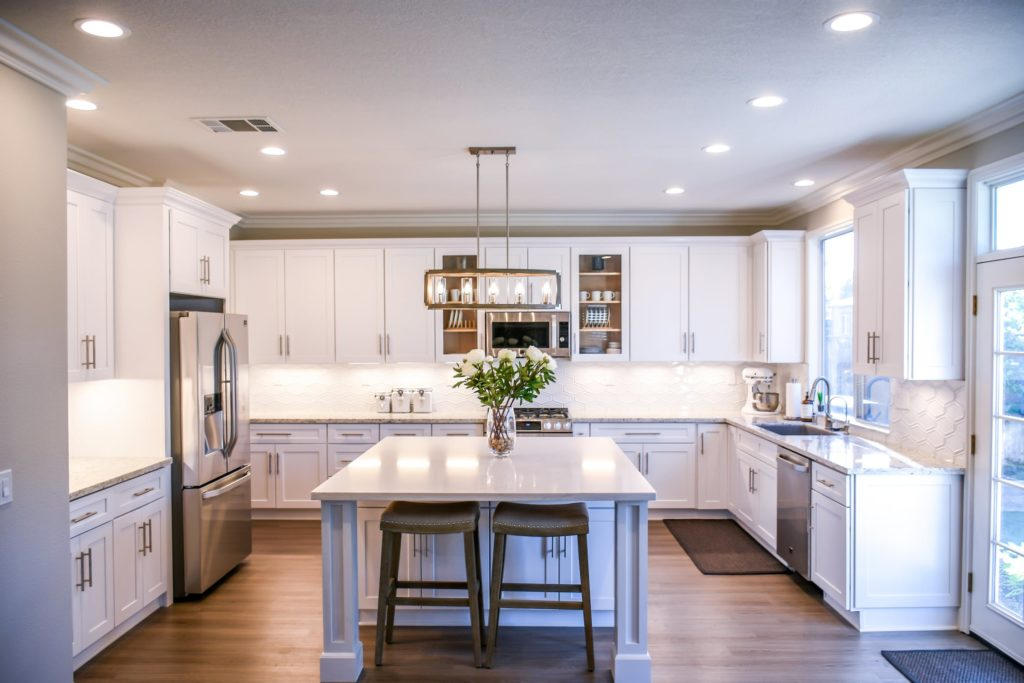 See how this hardwood floor adds value to an already beautiful kitchen space with white cabinets.